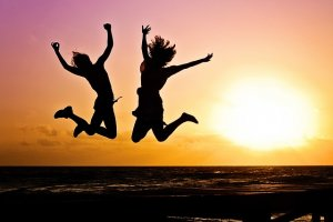 Picture of silhouettes jumping sunset corporate employee benefits